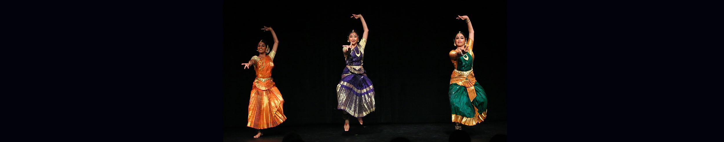 3 women dancing in colorful dresses