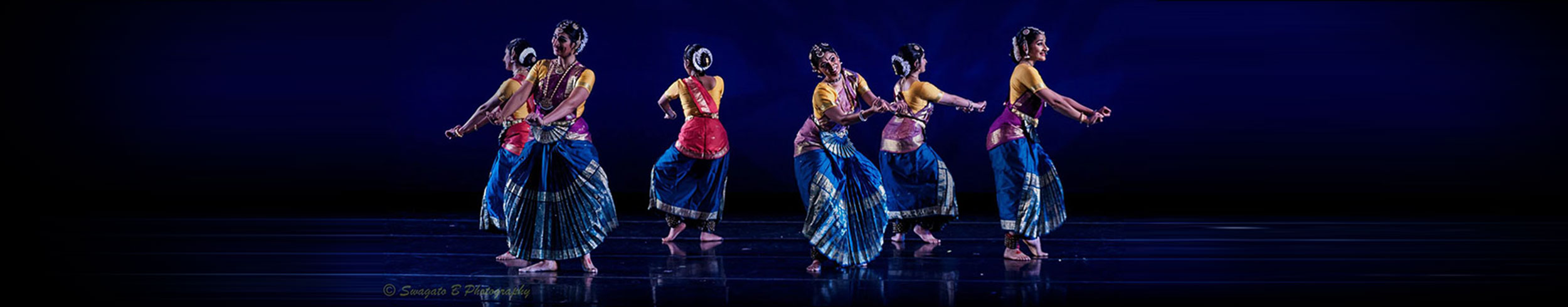 6 women dancing in a circle with colorful dresses